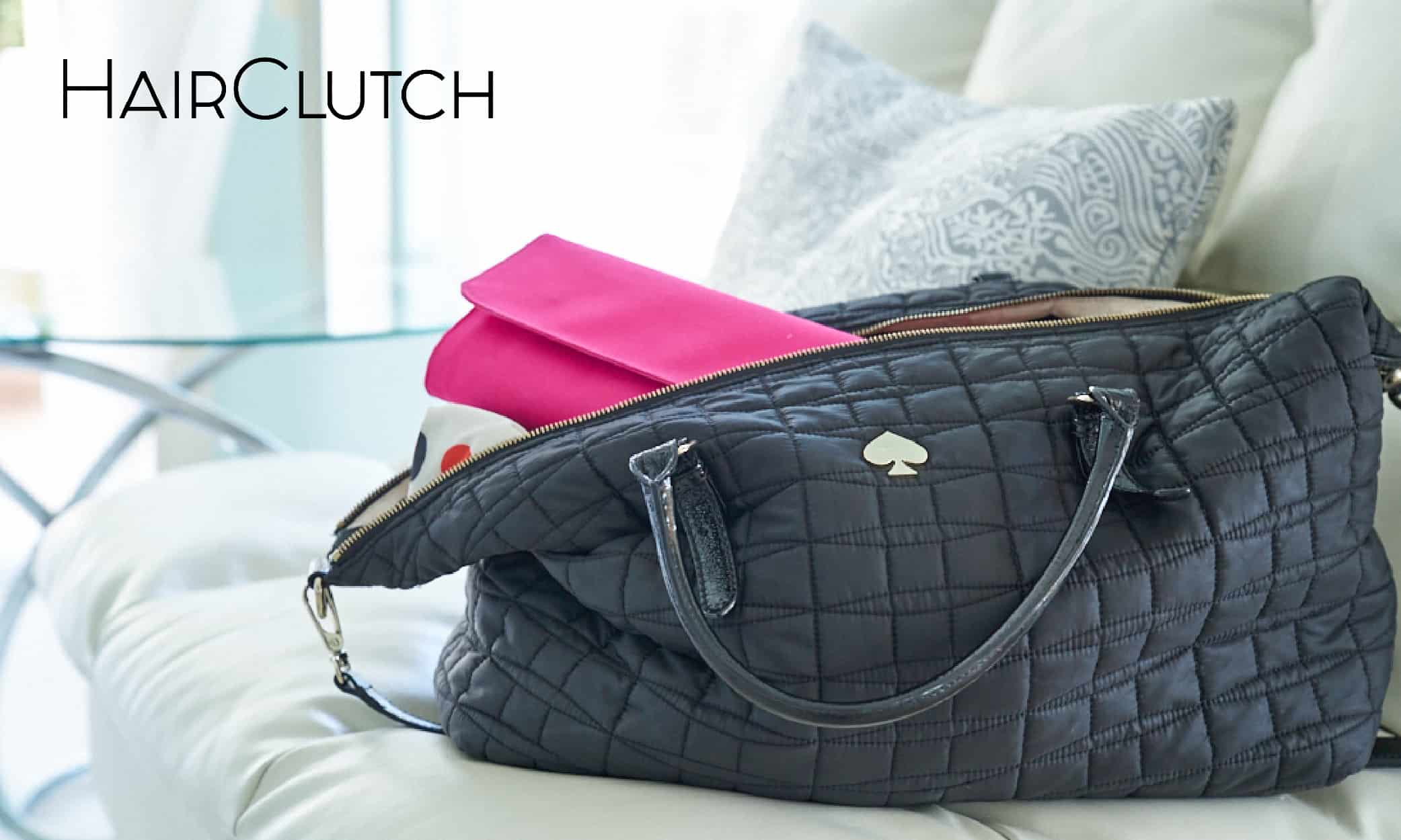 A black HairClutch purse back sitting on a couch
